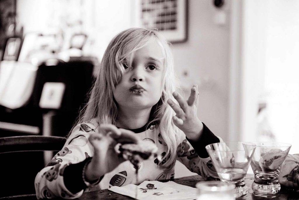 Little girl eating pancakes, black and white
