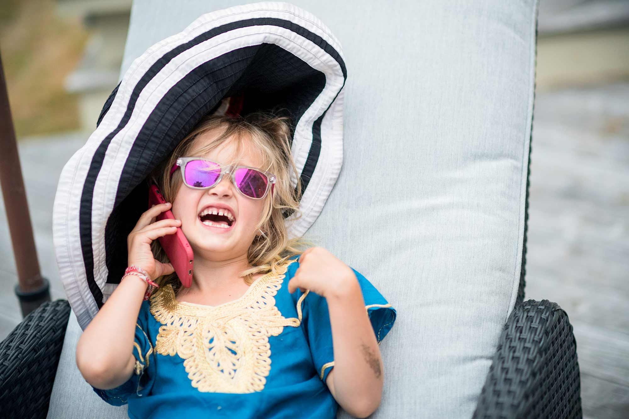 Little girl wearing sunglasses and big hat
