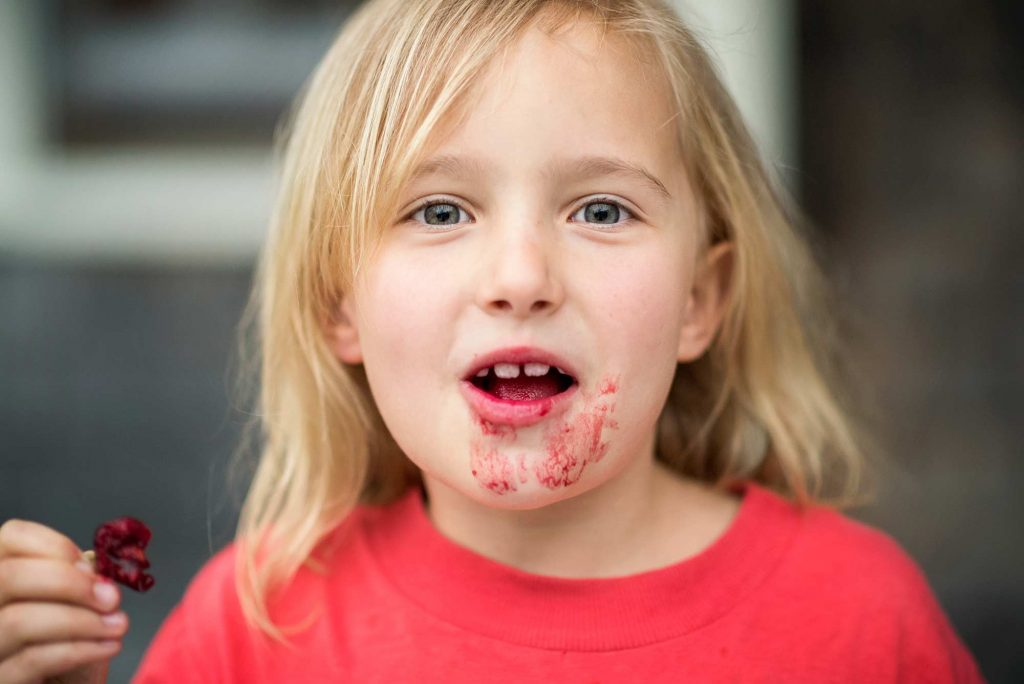 Little girl eating messy berries