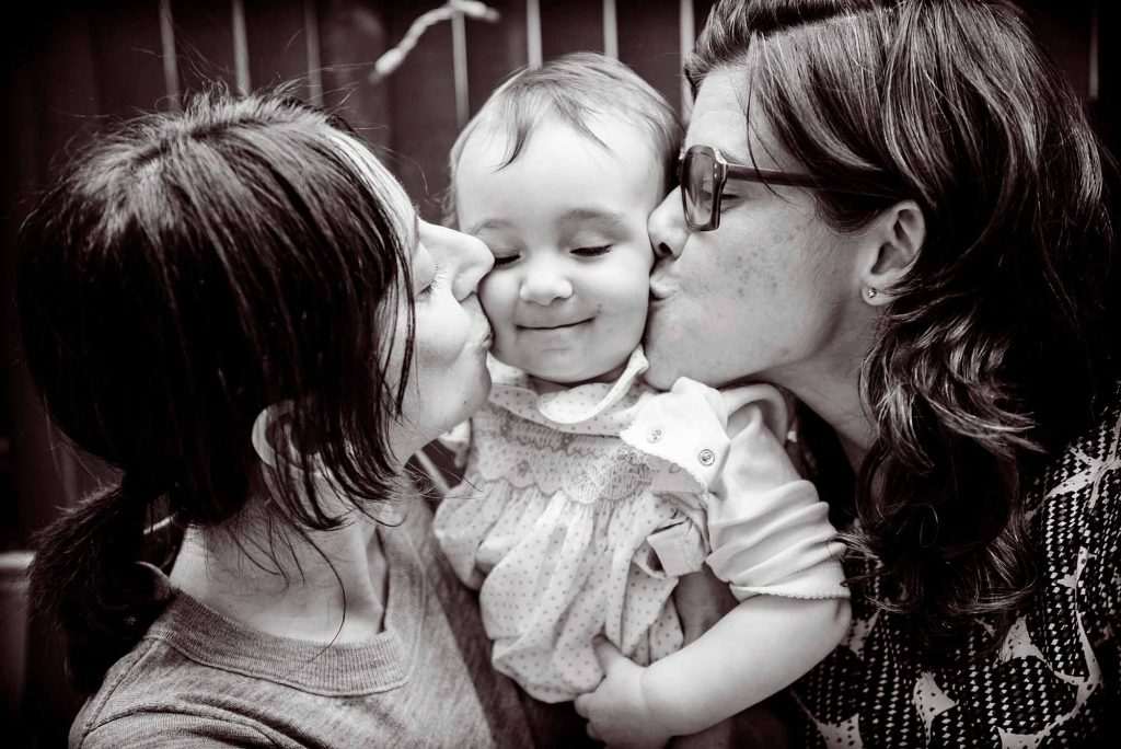 Baby being kissed by two mothers